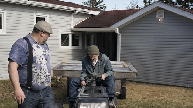 Un homme debout près de son père qui est assis sur un tracteur à gazon.