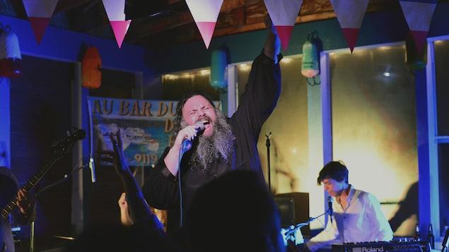 Un chanteur est sur scène devant une foule avec un bassiste et un claviériste. Il chante fort, les yeux fermés avec son poing soulevé au dessus de sa tête.
