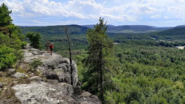 Deux hommes sont debout sur un cap de roche. Ils regardent les arbres à l'horizon et portent un casque de vélo.