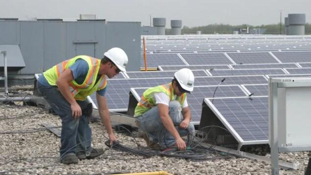 Deux hommes tiennent des câbles liés à des panneaux solaires sur un toit.