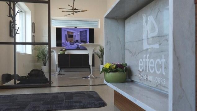 L'intérieur de l'immeuble. Au premier plan, il y a une enseigne en marbre et un pot de fleur. On voit des chaises blanches une télévision et des plantes à l'arrière.