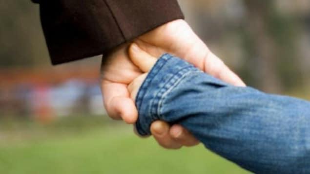 Photo d'une adulte qui tient la main d'un enfant.