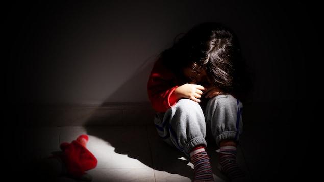Jeune fille assise seule dans le noir.