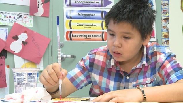 Enfant dans une salle de classe avec des dessins sur les murs.