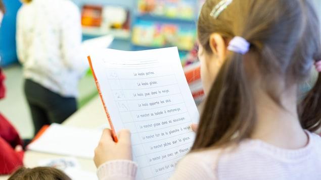 Une élève observe son exercice de français.