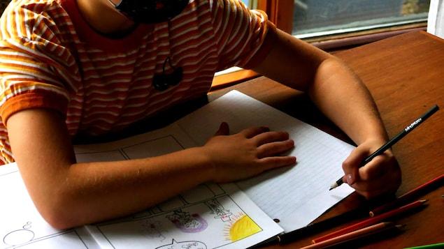 Un enfant, le visage à moitié masqué fait ses devoirs.