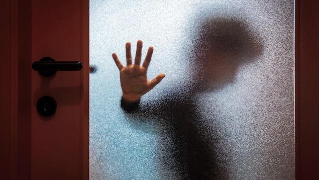Un enfant derrière une fenêtre givrée pose sa main contre la vitre en regardant au sol.