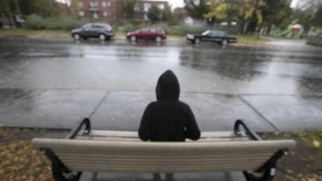 Un garçon est assis seul sur un banc au bord de la rue.