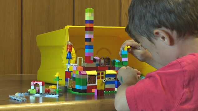 Un enfant joue aux Lego dans une école.