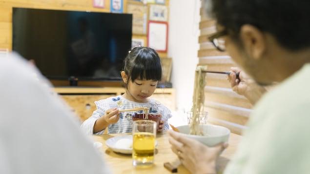 Jeune enfant mangeant une soupe de nouilles.