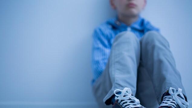 Un enfant dont on ne voit pas le visage est assis par terre