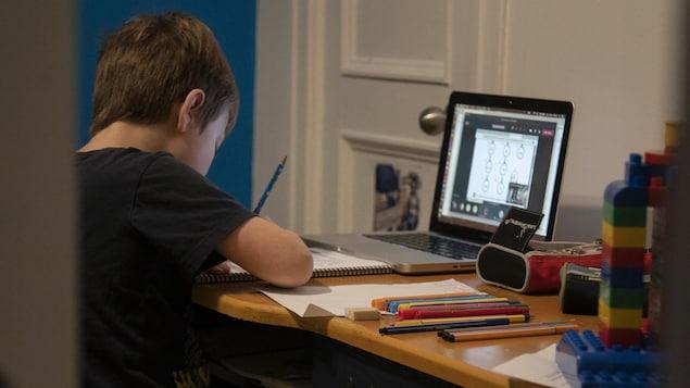Un jeune garçon fait ses devoirs devant un écran d'ordinateur.