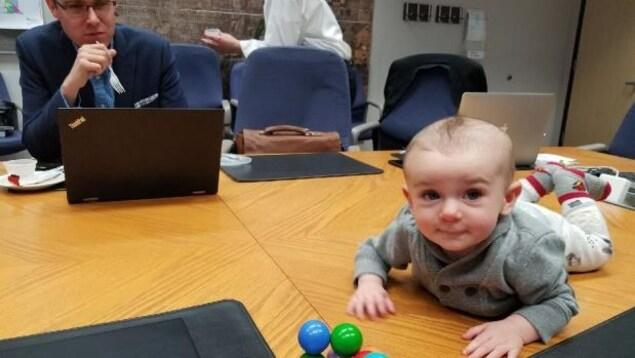 L'enfant joue à plat ventre sur la table de réunion.