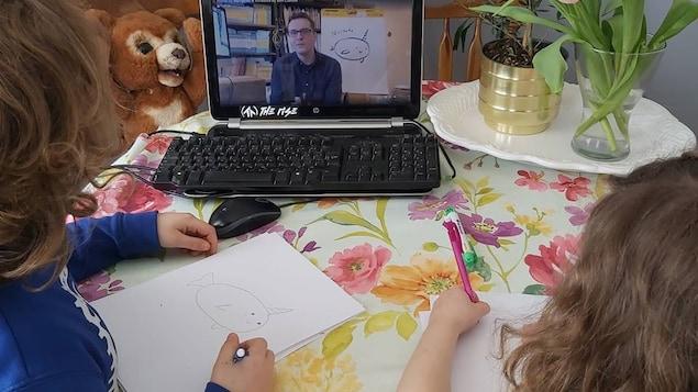 Deux petites filles regardent une vidéo, tout en dessinant.