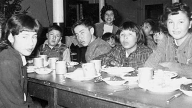 Des enfants prennent le repas au pensionnat de la réserve Gordon, géré par l'Église anglicane du Canada, en Saskatchewan, en 1945.
