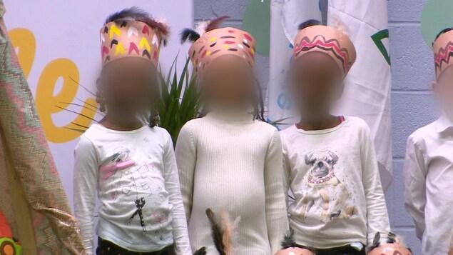 Trois fillettes portent des répliques d'une coiffe autochtone lors d'une cérémonie d'inauguration dans une école publique de Toronto.