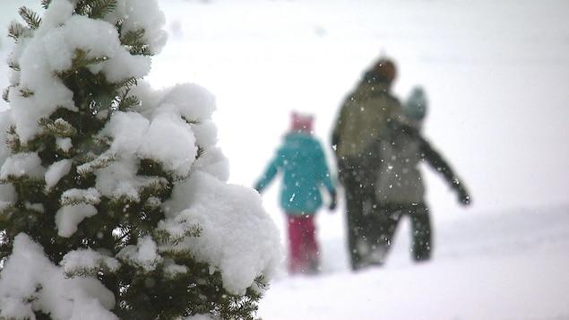Un père et ses deux enfants dans la neige.