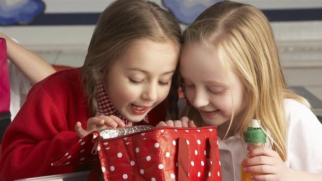 Des enfants regardent l'intérieur d'une boîte à lunch.