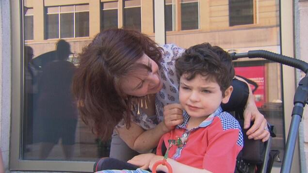 Une mère prend soin de son fils dans une poussette.