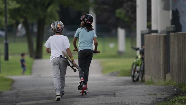 Une fillette se déplace en trottinette, tandis qu'un garçon la suit en tenant une planche à roulettes.