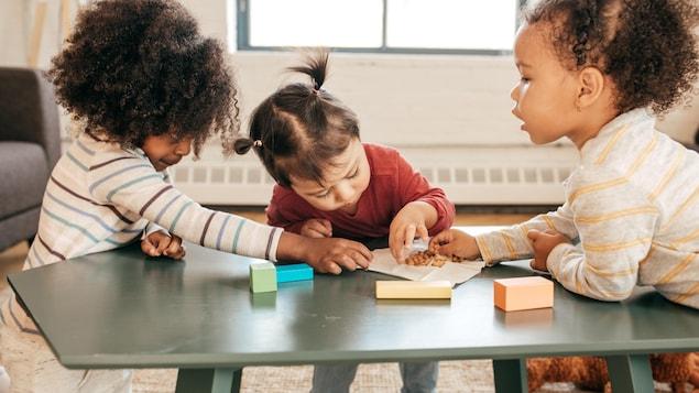 Trois fillettes jouent autour d'une table de salon.