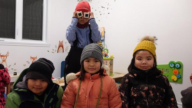 Des enfants habillés en hiver dans un local où il y a des jouets.