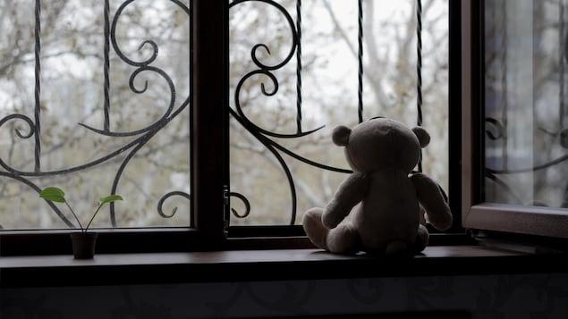Un ourson posé sur le rebord d'une fenêtre.