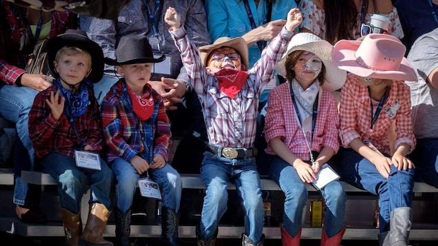 Un groupe d'enfants habillés en cow-boy regardent le défilé.
