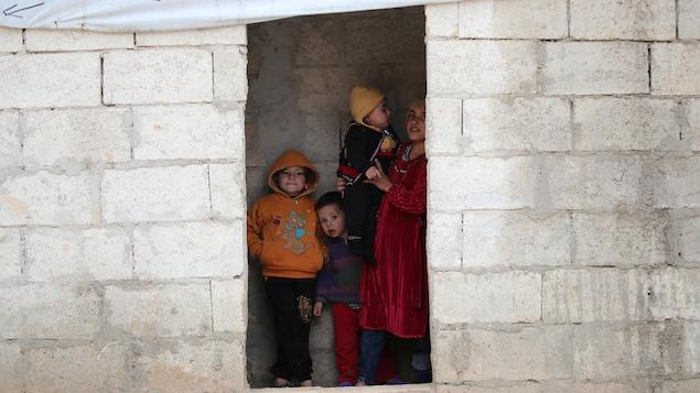 Quatre enfants se tiennent dans l'embrasure d'un bâtiment sans porte.