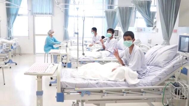 Trois des12 garçons rescapés posent dans une chambre d'hôpital en Thaïlande.