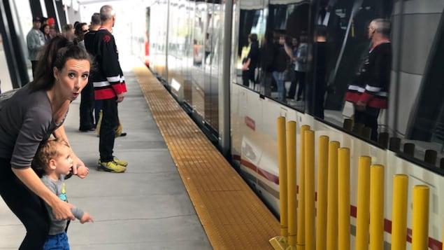 Plusieurs passagers, dont une mère et son enfant, sur le quai d'une station de la ligne de la Confédération d'Ottawa, en face d'un train.