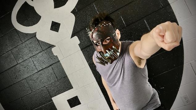 Un acteur qui porte un masque derrière sont masque de hockey.