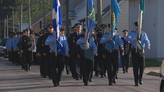 Gens qui défilent dans la rue en uniforme et des drapeaux.