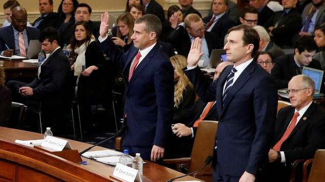 La main droite levée, Steve Castor et Daniel Goldman prêtent serment, plusieurs journalistes sont en arrière-plan.
