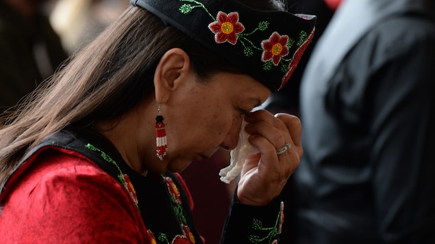 A woman cries with her head bowed and tries to wipe her tears with a white tissue.