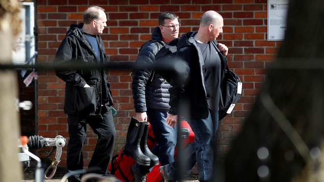 Trois hommes transportent des sacs près d'un immeuble en brique.