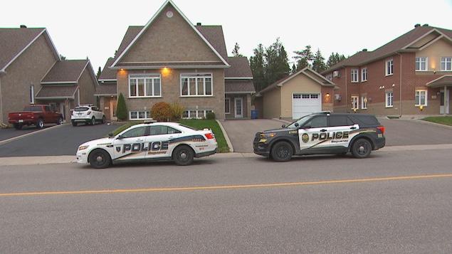 Deux véhicules de police devant la résidence.