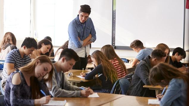 Un enseignant supervise le travail d'élèves du secondaire dans une classe.