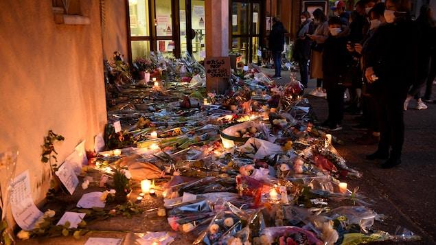Des gens se tiennent debout devant des gerbes de fleurs, des chandelles allumées et des pancarte, dont l'une indique «#Je suis prof #Je suis Samuel».
