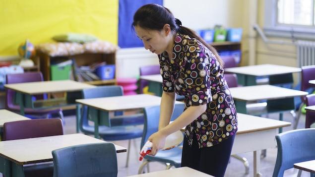 Une enseignante désinfecte un bureau.