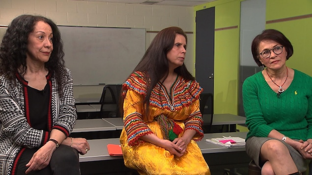 Trois femmes assises sur des bancs dans une école lors d'une entrevue télévisée. À gauche, Leïla Bensalem, porte un veston noir et blanc et un pantalon noir. Au centre, Djamila Addar porte une robe jaune traditionnel de la Kabylie. À droite, Leïla Lesbet, porte une veste verte et une jupe grise.