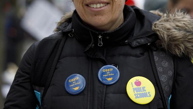 Une enseignante en grève qui porte des macarons