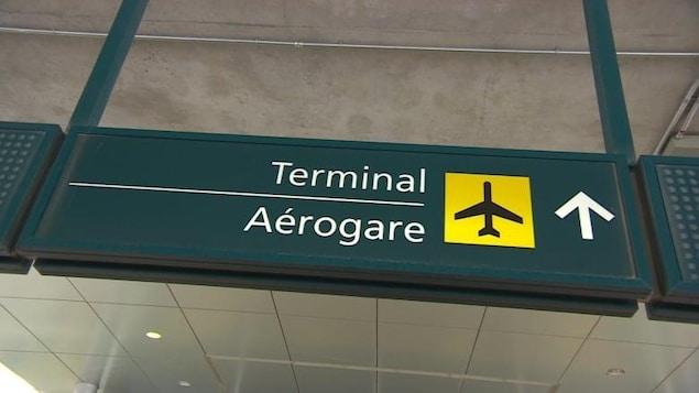 Un enseigne indiquant ka direction de l'aérogare dans un aéroport.