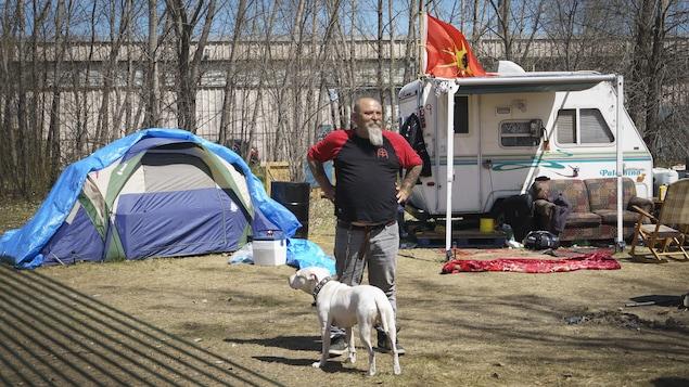 Guylain Levasseur se tient debout fièrement en compagnie de son chien, devant sa petite roulotte et sa tente.
