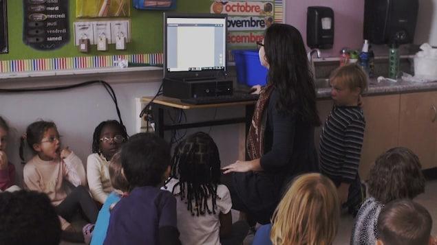 Des enfants et une femme sont dans une salle de classe et regardent vers un ordinateur.