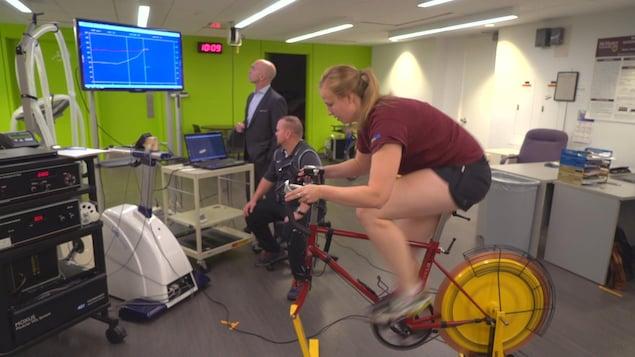 Une femme sprinte sur un vélo stationnaire dans le cadre d'une recherche sur l'entraînement physique.