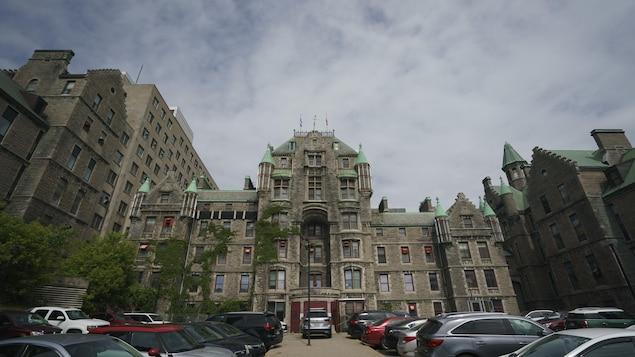L'entrée de l'ancien hôpital, on voit des voitures stationnées devant.