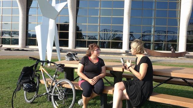 Deux femmes discutent, assises sur une table de pique-nique sur laquelle est appuyé un vélo.