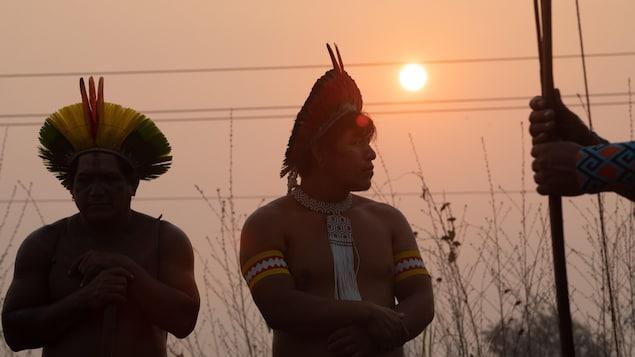 Trois Autochtones de l'Amazonie brésilienne en habits traditionnels se tiennent debout devant un coucher de soleil.