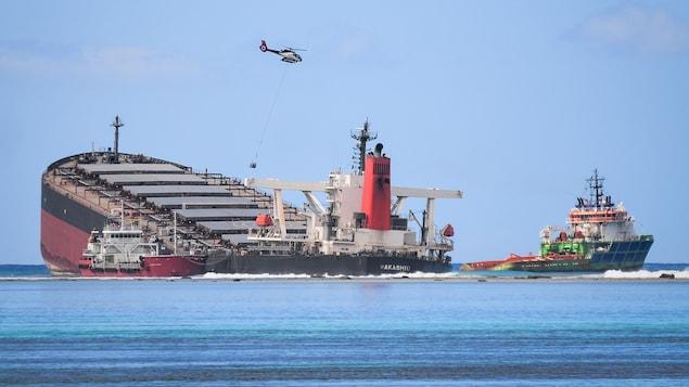 La partie avant du navire est surélevée alors que l'arrière sombre dans la mer.